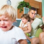 Young angry parents with two kids having quarrel at home. Focus on man